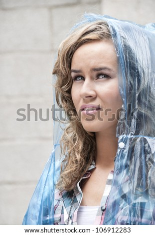 Young woman looking pensively up at the sky waiting for the rain - stock photo
