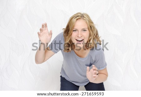 Young woman looking surprised on white background - stock photo