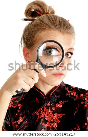 Young woman looking through a magnifying glass isolated over white - stock photo