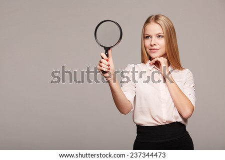 Young woman looking through a magnifying glass on a gray background - stock photo