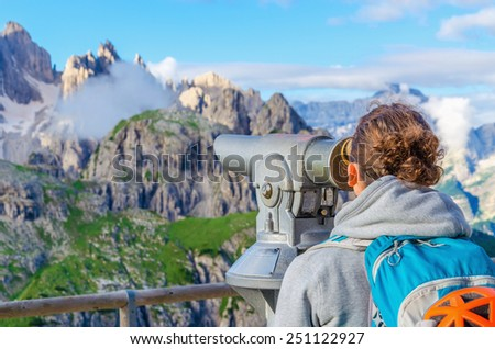 Young woman looking through binoculars at the wonderful view of the Dolomites Mountains, Dolomiti di Sesto or Sextner Dolomites, Italy - stock photo