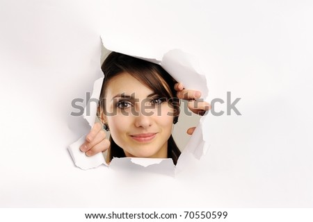 Young woman looking through hole in paper - stock photo