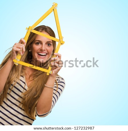 Young Woman Looking Through House Frame against a blue background - stock photo