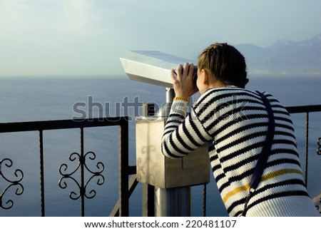 young woman looking through telescope at sea viewpoint in Ataturk park, sunny morning - stock photo