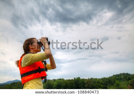 Young woman looking to sky through binoculars - stock photo