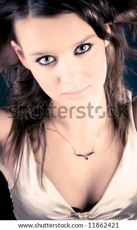 Young woman looking up. Studio portrait in yellow and blue colors. - stock photo