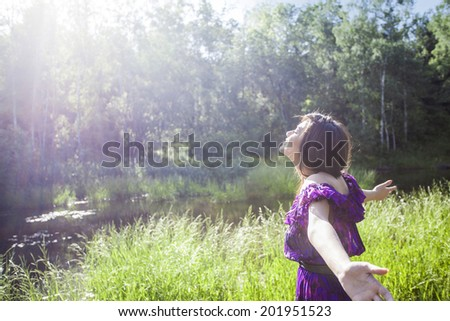young woman looking up to the sun near pool in the wood - stock photo