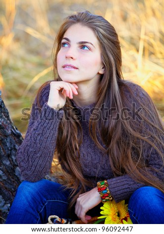 Young woman looking up while resting and thinking outdoor. - stock photo