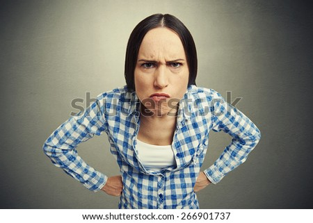 young woman looking with disapproval over dark background - stock photo