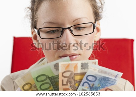 Young woman looks at a fan of money - stock photo