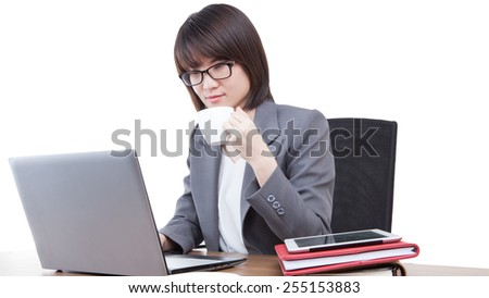 Young woman looks at laptop computer and drinks coffee at morning. Beautiful mixed asian / caucasian model. Isolated white background. - stock photo