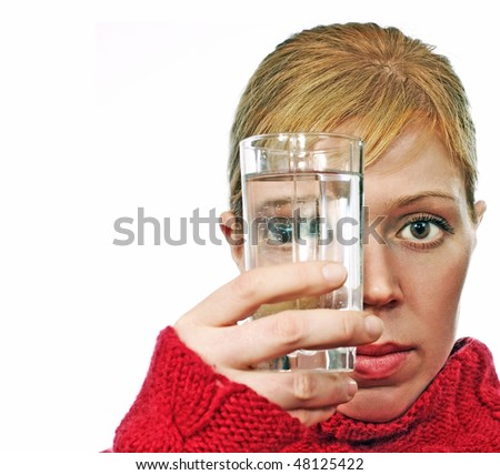 young woman looks through glass with water isolated over white - stock photo