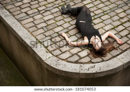 Young Woman Lying Down On Cobble Stone Road - stock photo