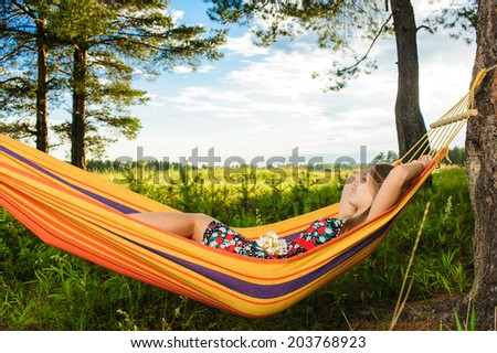Young woman lying in a hammock in garden with a bouquet of flowers of camomile - stock photo