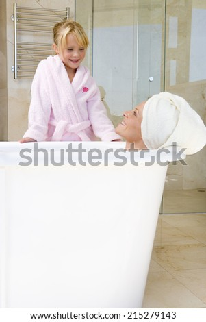 Young woman lying in bath, towel on head, smiling up at daughter (6-8) - stock photo