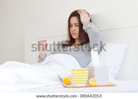 Young woman lying in bed and measuring body temperature - stock photo