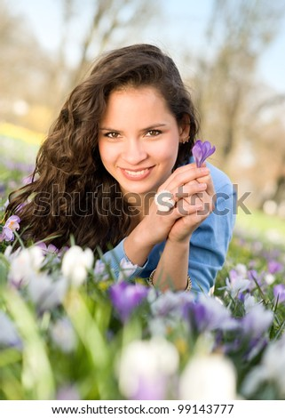 Young woman lying in flower meadow - stock photo
