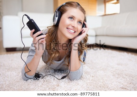 Young woman lying in the living room enjoying music - stock photo