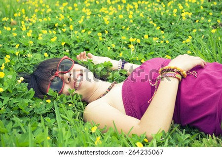 Young woman lying on a flowerbed looking up - stock photo