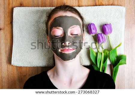 Young woman lying on a towel with a beauty mask and three tulips - stock photo