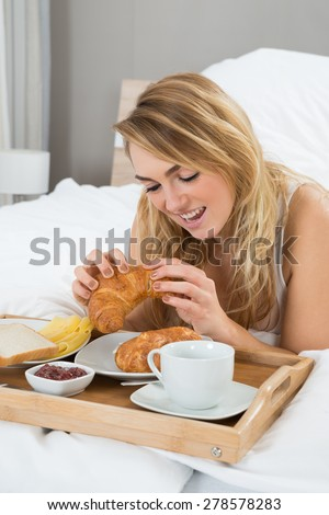 Young Woman Lying On Bed Having Breakfast - stock photo