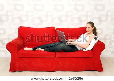 Young woman lying on couch with laptop - stock photo