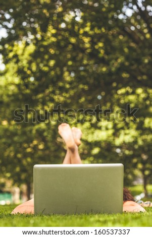 Young woman lying on grass in front of laptop at the park - stock photo