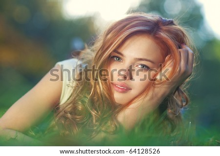 Young woman lying on grass portrait. - stock photo