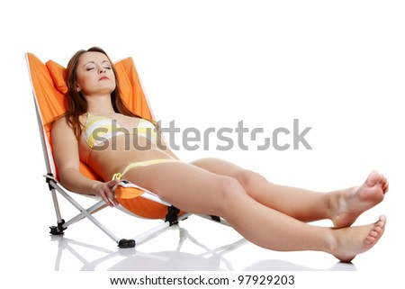 Young  woman lying on orange sunbed isolated over white background - stock photo