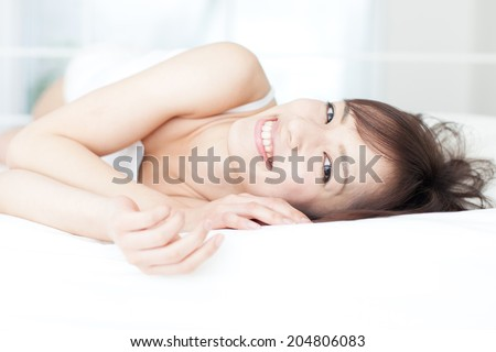 young woman lying on the bed - stock photo
