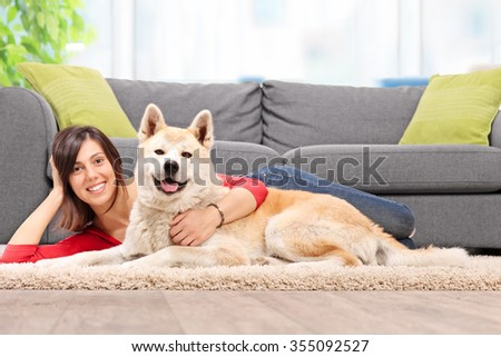 Young woman lying on the floor with her dog and hugging the dog by a gray couch at home shot with tilt and shift lens - stock photo
