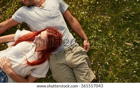 Young woman lying on the lawn with her boyfriend. Overhead view of young couple relaxing on the grass, with copy space. - stock photo