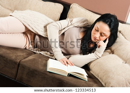 Young woman lying on the sofa and reading a book,Reading a book - stock photo