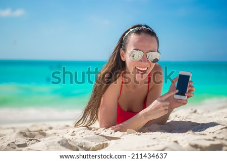 Young woman lying on white sand and talking by cell phone - stock photo