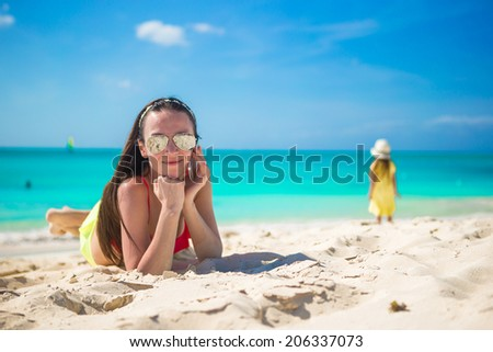 Young woman lying on white sand and talking by her phone - stock photo