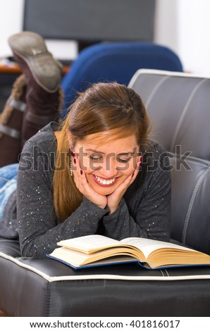 Young woman lying stomach down on dark sofa, supporting head using hands, reading and smiling - stock photo