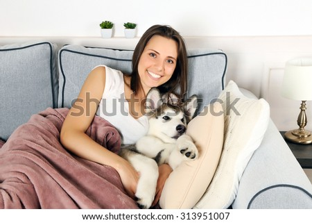 Young woman lying with malamute dog on sofa in room - stock photo