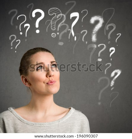 Young woman makes a face and thinking with question marks over head - stock photo