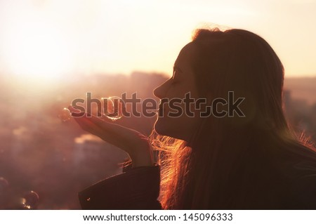 Young woman makes a wish. Cityscape background at sunset. - stock photo