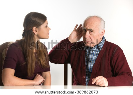 young woman makes hearing test for old senior man - stock photo