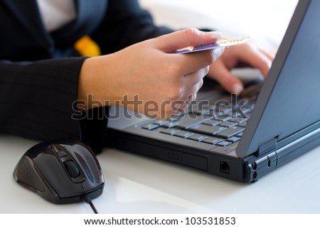 Young woman making a card payment on the internet on-line shopping - stock photo