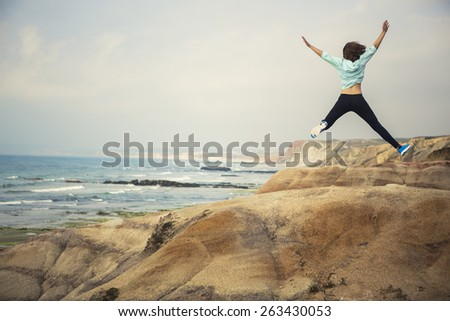 Young woman making a jump with a beautiful beach on the background - stock photo