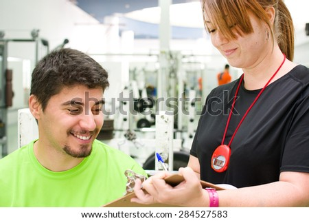 young woman making a training plan to a man at the gym - stock photo