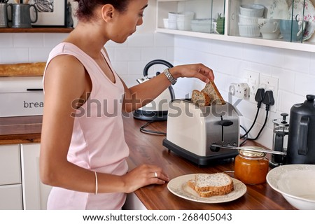 young woman making breakfast toast bread with toaster at home kitchen - stock photo