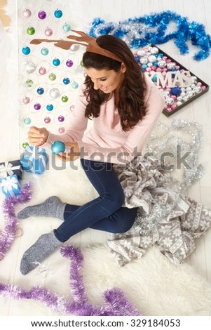 Young woman making christmas arrangements. Photographed from above. - stock photo