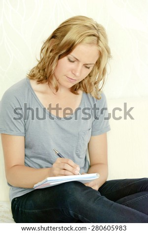 Young woman making notes in notebook - stock photo
