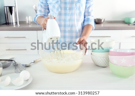 Young woman making rainbow cake in kitchen - stock photo