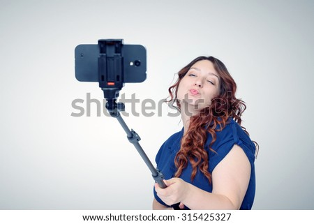 Young woman making selfie with a stick - stock photo