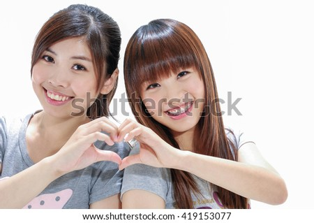 Young woman making the shape of a heart with hands  - stock photo