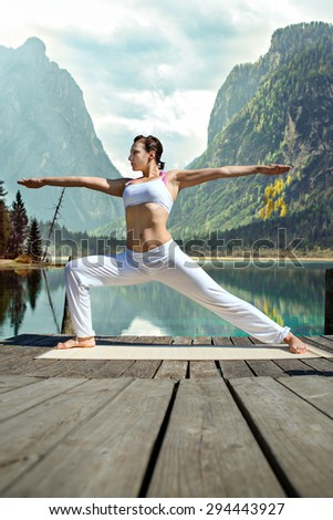 young woman making yoga exercise at a lake - stock photo